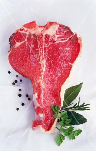 A T-bone steak, peppercorns and herbs