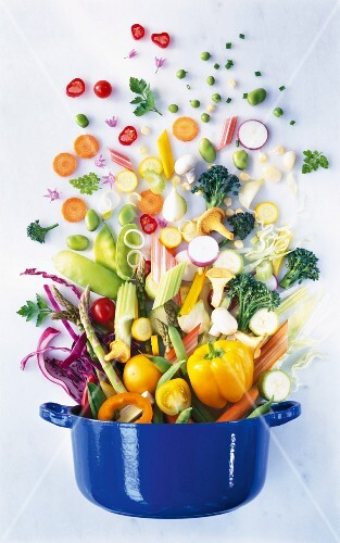 Various types of vegetables falling into a pot