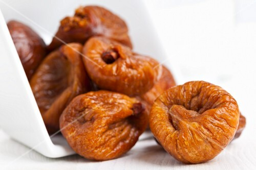 Dried figs falling out of a bowl