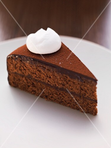 A slice of chocolate cake with a dollop of cream