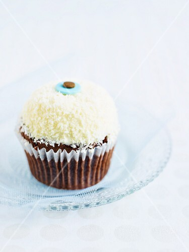 A cupcake decorated with coconut sprinkles and butter cream