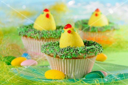 Easter cupcakes decorated with Easter eggs and green sprinkles