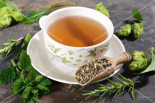 A cup of herbal tea surrounded by ingredients