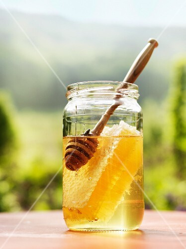 A jar of honey with a honeycomb and a honey spoon