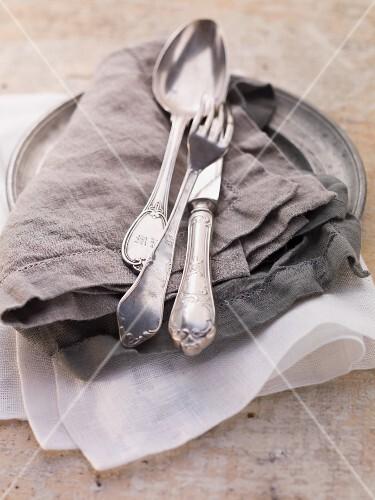 Cutlery on a linen napkin on a zinc plate