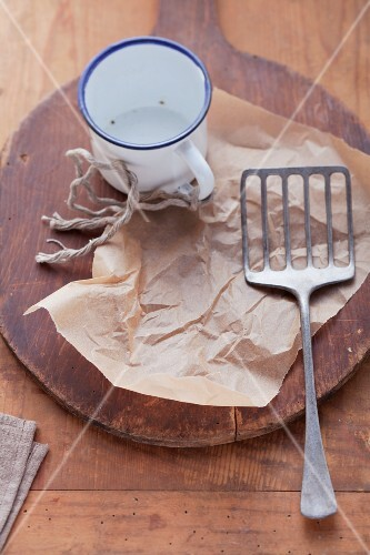 A spatula, baking paper and an enamel cup on a wooden board