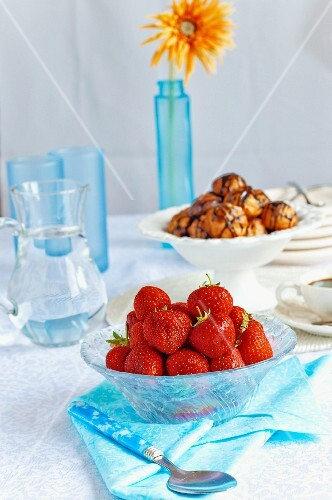 Fresh strawberries in a glass bowl with a jug of water and profiteroles
