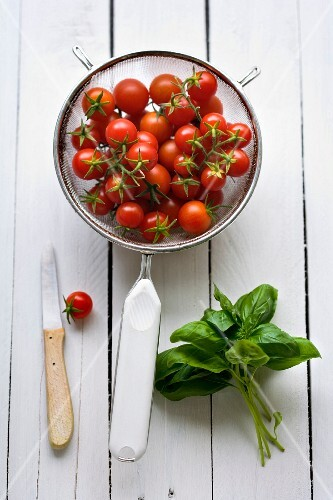 Cherry tomatoes in a sieve with a bunch of fresh basil next to it