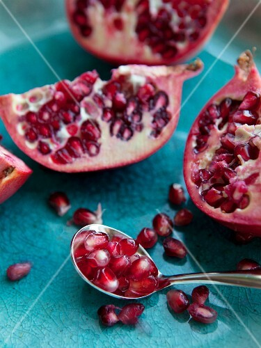 Sliced pomegranates and pomegranate seeds