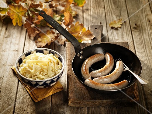 Pork sausages in a pan with tagliatelle