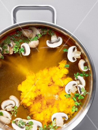 Thick mushrooms soup in a pot (seen from above)