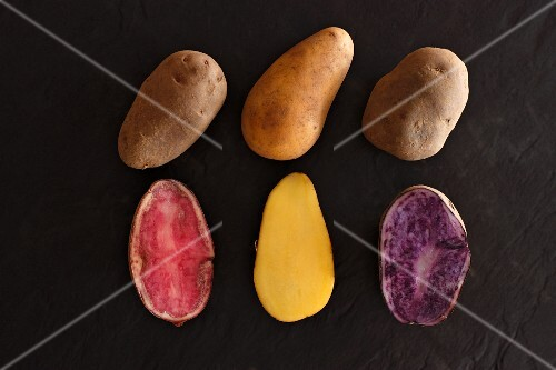 Various different types of potatoes on a slate surface