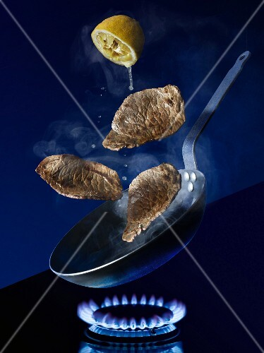 Escalopes in a pan on a stove being drizzled with lemon juice