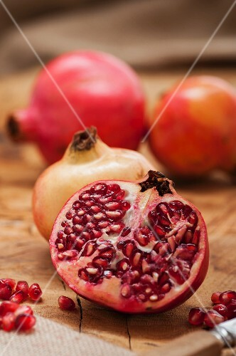 Pomegranates, whole and halved with seeds