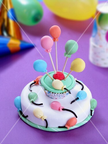 A cake decorated with balloons for baby party