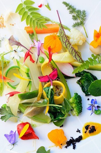 Chopped vegetables and flowers on a white plate