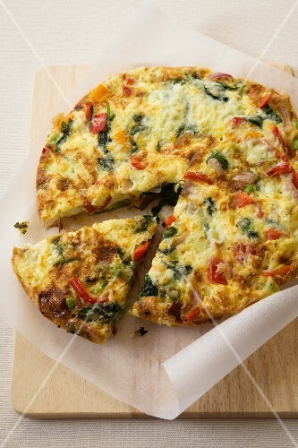 Vegetable Spanish Tortilla with Slice Removed; On a Cutting Board