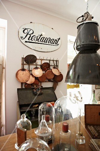 Old restaurant sign above collection of shiny copper pans hanging on wall rack; several bell jars in foreground