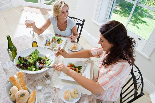 Two women having lunch at table, smiling, elevated view
