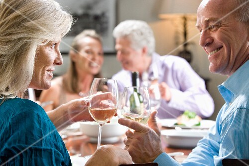 Mature couple toasting wine glasses at dinner table, mature couple smiling in background