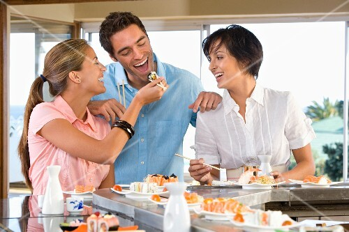 Three friends eating in sushi bar, smiling