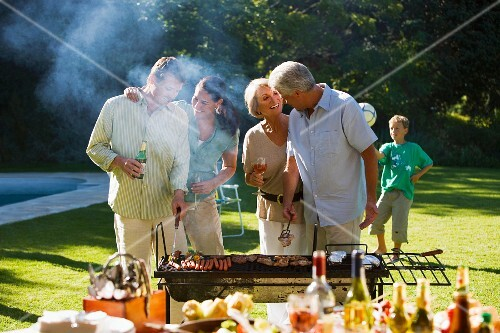 Three generation family having barbecue in summer garden, adults standing beside barbecue grill, grilling meat, children (8-10) playing in background