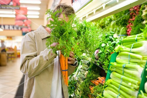 Man choosing carrots in grocery store