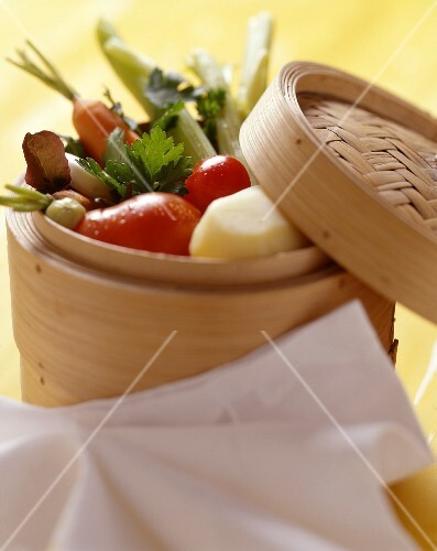 A selection of vegetables displayed in a bamboo steamer