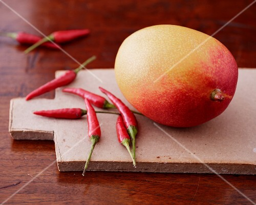 A mango and red chillis on a wooden board