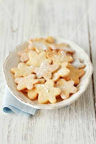 Flower-shaped biscuits dusted with icing sugar
