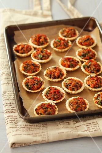 Ham and mushroom tartlets on a baking tray