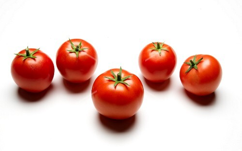 Five Whole Red Tomatoes on a White Background