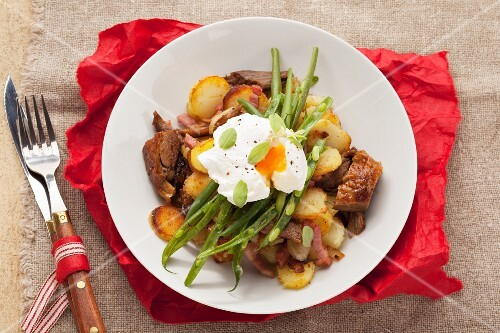 Gröstl (typical Tirolean dish using leftovers) with potatoes, pork, green beans and a poached egg
