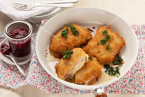 Chicken Cordon Bleu in a frying pan, with cranberry jelly as a condiment