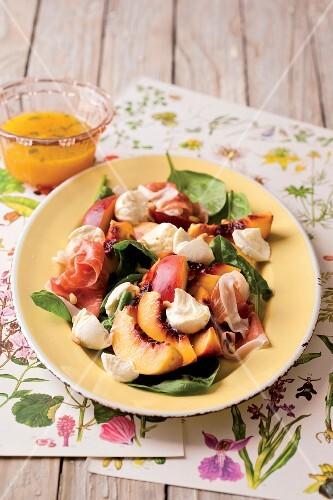 Spinach salad with mozzarella, ham and peaches