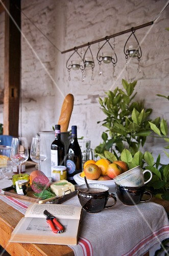 Table set with fruit bowl, wine, bread, cheese and cold meat against whitewashed, rustic brick wall