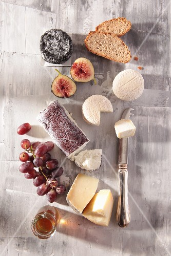 Still life of cheese with grapes, figs, honey and bread