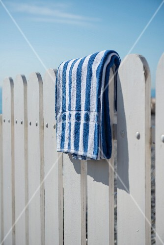 Blue and white striped towel on a white wooden fence at the beach