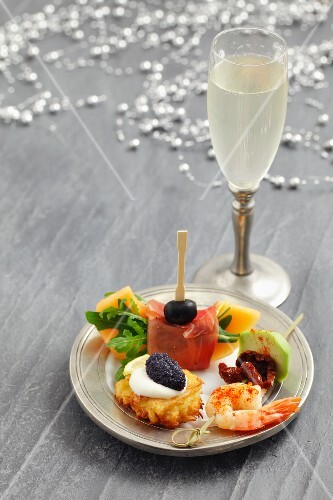 A plate of Christmassy appetisers and a glass of sparkling wine
