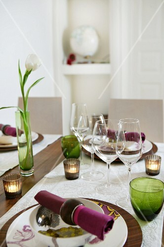 Tealight holders and tulip in vase on set table