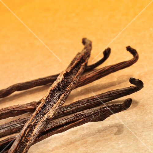 A number of vanilla pods on yellow stone