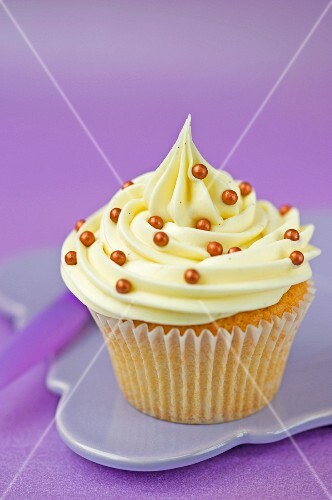 A cupcake with vanilla icing and gold sugar pearls in a paper case
