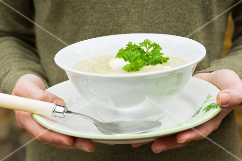 A woman holding a bowl of celery soup with crème fraîche and parsley
