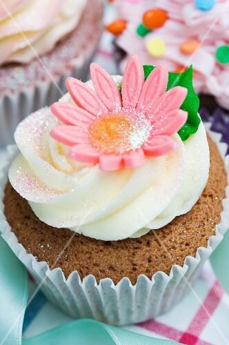 A vanilla cupcake with a pink sugar flower
