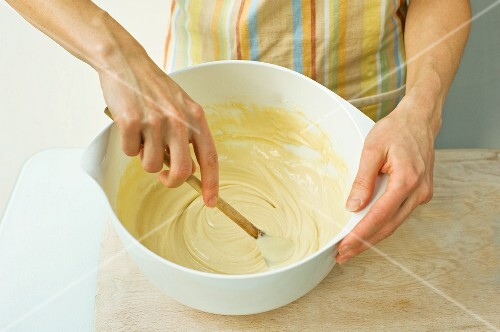 A woman mixes batter with a wooden spoon in a bowl