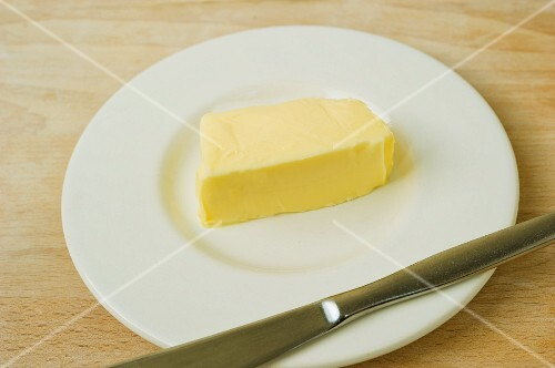 A pat of butter on a plate with a knife