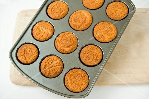 Vanilla muffins in a muffin tin on a chopping board