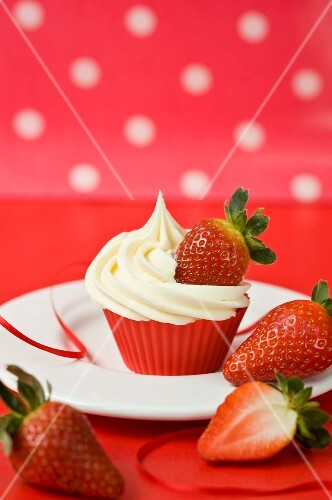 A cupcake with vanilla icing and fresh strawberries