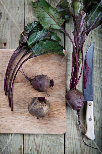 Beetroot and beetroot leaves on a chopping board, and a knife on a wooden surface