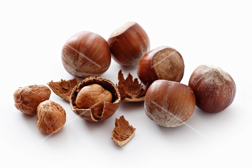A number of whole hazelnuts and hazelnut shells